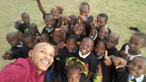 """Kenyan children repping for the cause with their """"World Peace Before 2021"""" tee-shirts."""